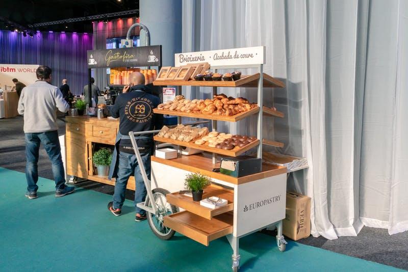 ▲IBTM World Barcelona:パンやコーヒーを片手に仕事をしている人