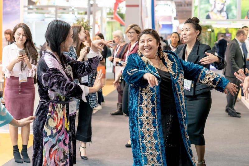 ▲IBTM World Barcelona:参加者と一緒にダンスを踊るカザフスタンブースの担当者