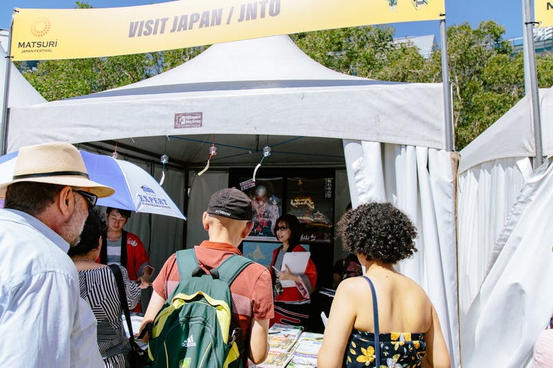 ▲Matsuri-Japan Festival:パンフレット説明をするスタッフと持っていくものを吟味する来場者